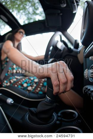 Woman driving, hand on stick shift