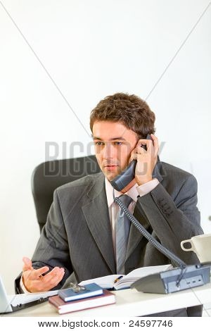 Serious Modern Businessman Sitting At Office Desk And Speaking Phone
