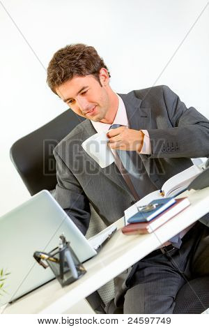 Happy Modern Businessman Drinking Coffee And Looking In Laptop