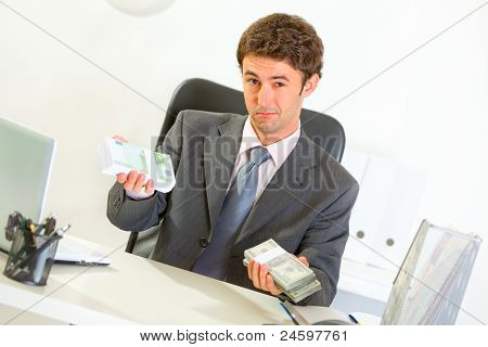 Authoritative Businessman Sitting At Office Desk And Offering Money Packs