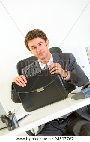 Confident Businessman Sitting At Office Desk With Briefcase