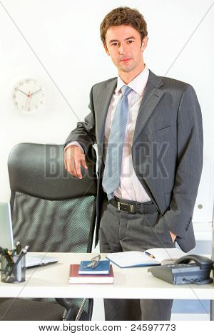 Portrait Of Confident Modern Businessman Standing At Office Desk