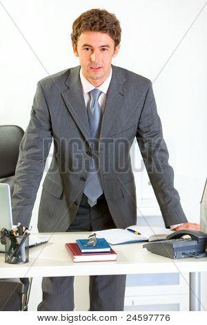 Retrato de empresario moderno seguro agarrados de la mano en el escritorio de oficina