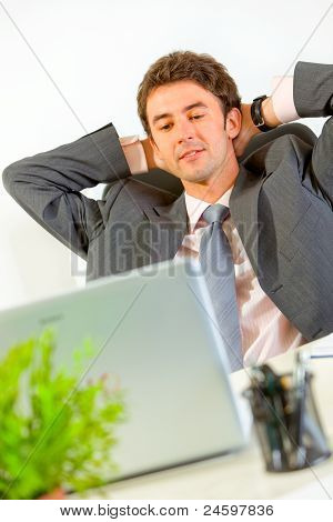 Pleased Businessman Relaxing On Office Armchair And Looking In Laptop
