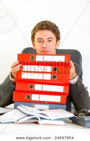 Sitting At Office Desk Confused Businessman Looking Out From Pile Of Folders