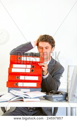 Confused Businessman Sitting At Office Desk With Pile Of Folders