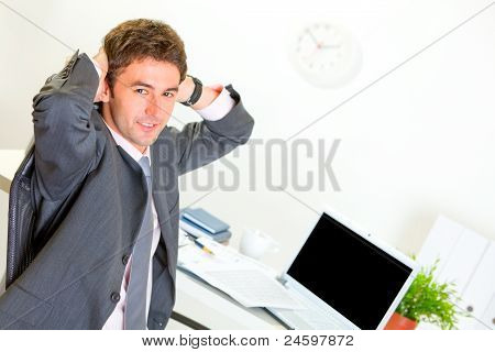 Pleased Businessman Relaxing On Armchair At Office Desk