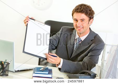 Smiling Businessman Giving Clipboard And Pen For Signing