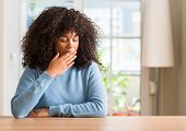 African american woman at home bored yawning tired covering mouth with hand. Restless and sleepiness poster