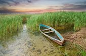 stock photo of boggy  - Boat at coast on sunset - JPG