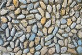 Wall Round Stone Rock Texture Background. Background Of Colored Smooth Stones. Texture Background Of poster