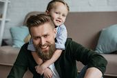 Portrait Of Little Son Hugging Smiling Bearded Father At Home poster