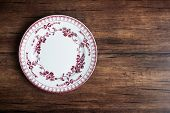 Empty White Dessert Plate With Red Floral Pattern On An Old Wooden Brown Background, Top View. Image poster