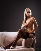 stock photo of braless  - Topless blond holding her breasts while sitting on a sofa - JPG