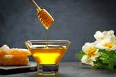 Honey With Wooden Honey Dipper On Wooden Table poster