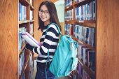 Education First, Beautiful Female College Student Holding Her Books Smiling Happily Standing In Libr poster