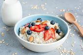 Oatmeal Porridge In A Blue Bowl With Berries And Nuts. Porridge Oats Bowl With Strawberries Blueberr poster