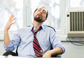 Nervous businessman working in a very hot office, he is sweating and loosening his tie poster