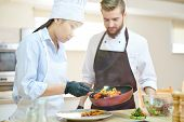 Portrait Of Female Asian Chef Cooking Delicious Dishes While Working In Modern Restaurant Kitchen Wi poster