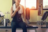 Female Athletes Listen To Music Using The Phone While Relaxi From Exercise. Asian Athlete In Sports  poster