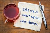 Old ways will not open new doors - handwriting on a napkin with a cup of tea. poster