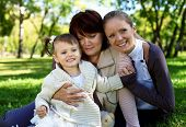 image of family fun  - Grandmother with daughter and granddaghter in green summer park - JPG