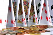 image of shaky  - Castle of cards next to a pile of coins - JPG