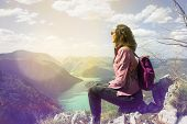 Girl Relaxing On A Beautiful Mountain View. Traveler Sitting On Mountain Rock Enjoying Beautiful Mou poster