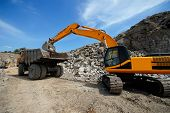 Universal Excavator Loads Granite Stones In A Dumper. Loading In An Industrial Pit For The Extractio poster