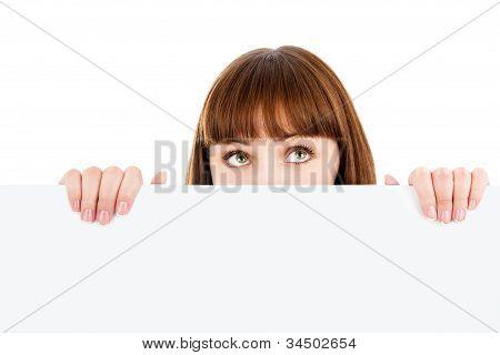 Pensive Woman Peeking Over Blank Billboard