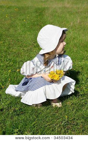 Beautiful Little Girl Wearing Dress With Yellow Dandelions Sits On Grass And Looks Into Distance