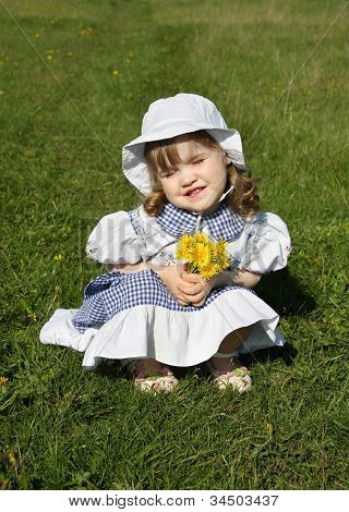Beautiful Little Girl Wearing Dress With Yellow Dandelions Sits On Grass And Blinks Sun