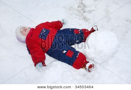 Little Tired Girl Wearing Warm Jumpsuit Lies On Snow Near Big Snowball