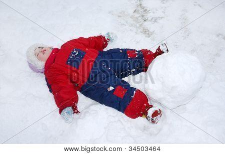Little Tired Girl Wearing Warm Jumpsuit Lies On Snow Near Big Snowball