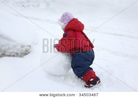 Back Of Little Girl Wearing Warm Jumpsuit Is Rolling Big Snowball