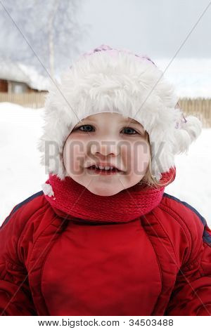 Cute Little Girl Wearing Warm Clothing Stands Near Home And Smiles