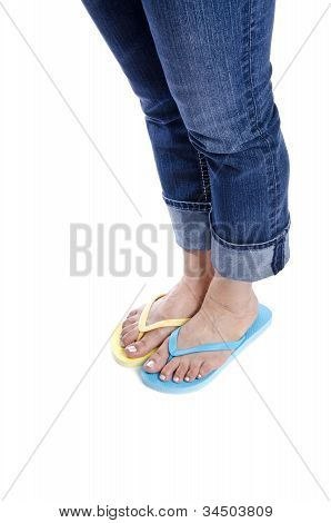 Woman Wearing Blue Jeans and Mismatched Flip Flop