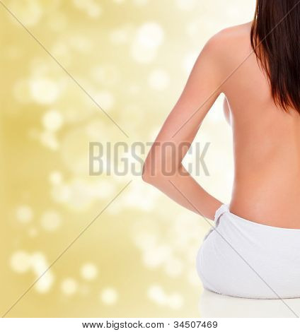 Naked female back on blurred background.