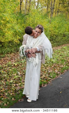 Young Groom Hugs His Beautiful Bride With Roses And Kisses Neck In Autumn Park
