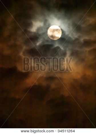 Spooky Moon. Reflections of a full moon producing orange brownish shadows on the surrounding clouds.