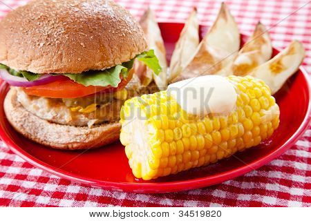Healthy turkey burger on whole grain bun, with baked potato wedges and corn on the cob. Low fat picnic options.