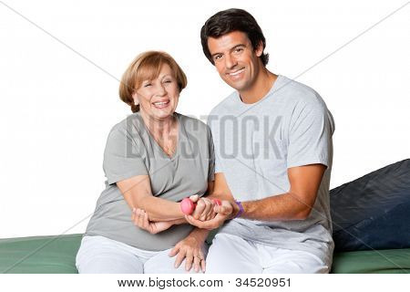 Portrait of happy young therapist giving muscle training for elbow joint over white background