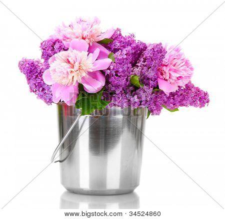 hermosas flores lila y peonías en cubo de metal aislado en blanco