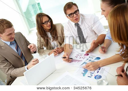 Image of confident partners sharing new ideas at meeting