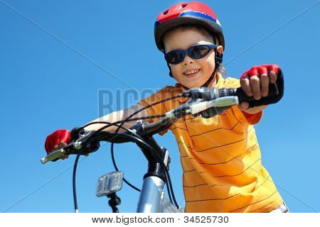 Cheerful little guy in protective sportswear riding a bike
