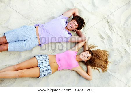 Above angle of teenage couple lying on sandy beach and laughing