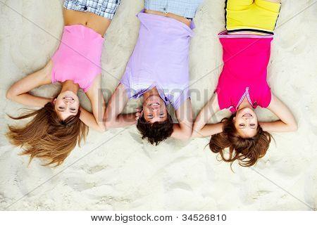 Por encima del ángulo de la risa de amigos adolescentes acostado en la playa