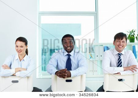 Portrait of successful business team sitting on chairs and looking at camera