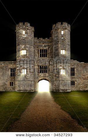 alte Burg bei Nacht mit Lichtern durchscheinen der offenen Tür