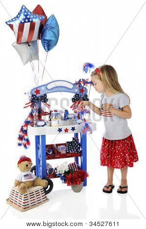 An adorable preschooler checking her Fourth of July vendor stand.  The stand's signs are left blank for  your text.  On a white background.